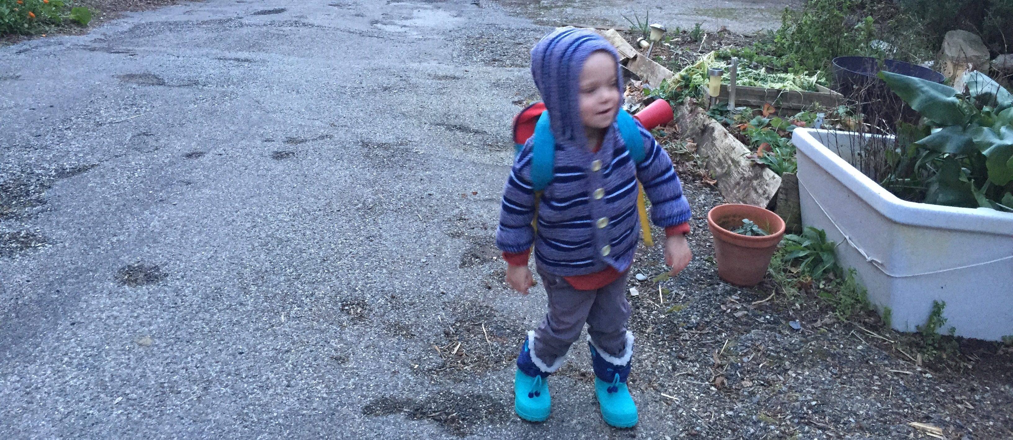 A small boy wearing a cardigan and carrying his rucksack